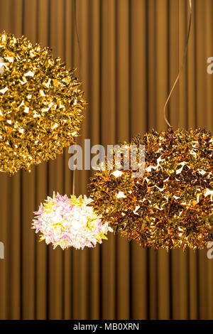 Fancy hanging metallic golden lamps with on a brown curtain wall background indoors. - Stock Photo