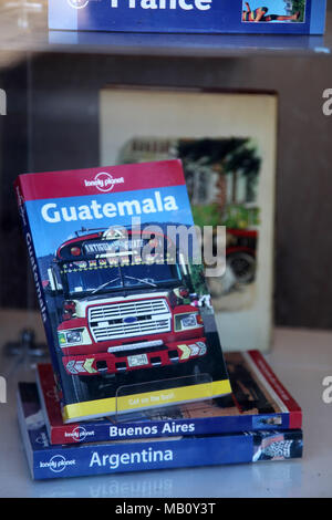Old travel guides in the window of a second hand bookshop - Stock Photo