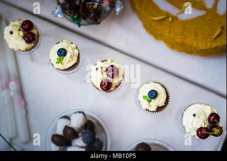 Berry cream coated muffins - Stock Photo
