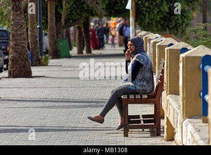 Aqaba, Jordan, March 7, 2018: Muslim young woman sitting on a bench on the beach promenade of Aqaba talking on her mobile phone, middle east - Stock Photo
