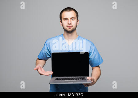 Portrait of a happy male doctor dressed in uniform with stethoscope showing blank screen laptop computer isolated - Stock Photo