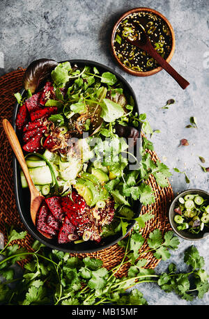 Asian red dragon fruit vegetarian salad. topped with fried spring onions and a asian dressing. - Stock Photo