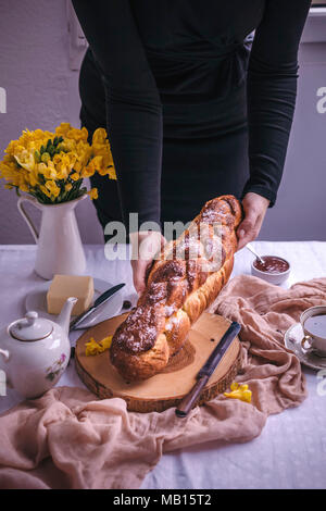 Woman holding a braided sweet Easter bread served for breakfast with butter and jam - Stock Photo