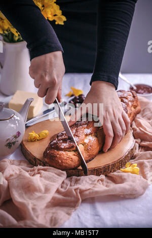 Woman slicing Braided sweet Easter bread served for breakfast with butter and jam - Stock Photo