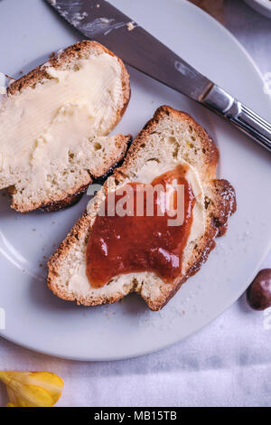 Braided sweet Easter bread served for breakfast with butter and jam - Stock Photo