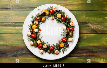 Rosemary wreath christmas appetizer with cheese and olives on plate on wooden background - Stock Photo