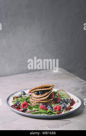 Vegan chickpea pancakes served in plate with green salad young beetroot leaves, sprouts, berries, berry sauce over grey kitchen table. Copy space. Hea - Stock Photo