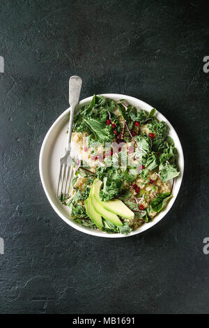 Vegan quinoa salad with kale, young beetroot leaves, garnet seeds, sliced avocado in white plate with fork over dark texture background. Top view, spa - Stock Photo