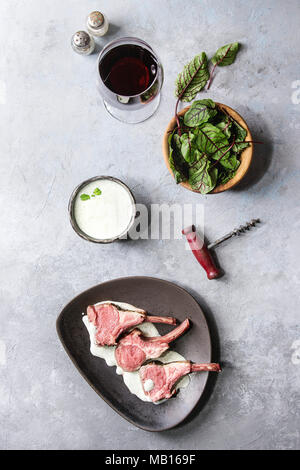 Grilled sliced rack of lamb with yogurt mint sauce served with green salad young beetroot leaves, glass of red wine, pink salt on round wooden slate b - Stock Photo