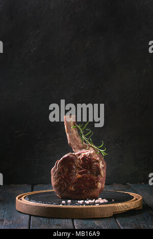 Grilled black angus beef tomahawk steak on bone served with salt, pepper and rosemary on round slate cutting board over dark wooden plank kitchen tabl - Stock Photo