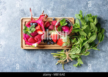Vegan fruit salad with berries and mint served in pink dragon fruit with ingredients above on wooden serving board over blue texture background. Top v