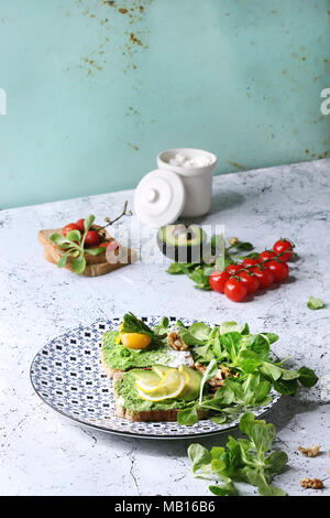 Vegetarian sandwiches with avocado, ricotta, egg yolk, spinach, cherry tomatoes on whole grain toast bread on ceramic plate with ingredients above ove - Stock Photo