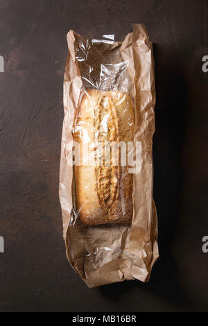 Loaf of fresh baked artisan white bread in market paper bag over dark brown texture background. Top view, copy space. - Stock Photo