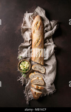 Loaf of sliced fresh baked artisan baguette bread on linen cloth with butter and herbsover dark brown texture background. Top view, copy space. - Stock Photo