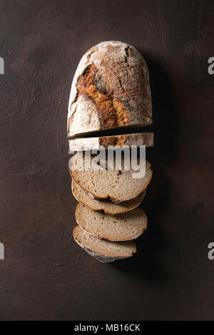 Sliced grilled sous-vide black angus beef tomahawk steak on bone served with salt, pepper, rosemary and white sauce on round wooden slate cutting boar - Stock Photo