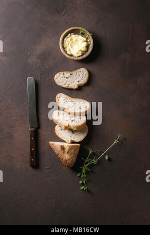 Loaf of fresh baked sliced artisan baguette bread with butter, herbs and vintage knife on wooden slate serving board over dark brown texture backgroun - Stock Photo