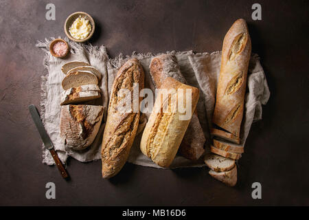 Variety of loafs fresh baked artisan rye, white and whole grain bread on linen cloth with butter, pink salt and vintage knife over dark brown texture  - Stock Photo
