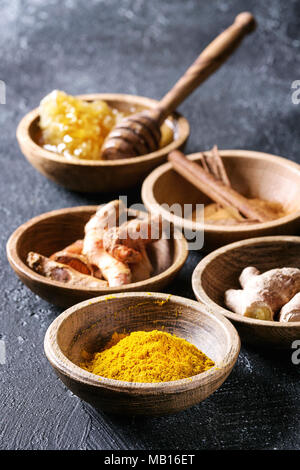 Ingredients for turmeric latte. Ground turmeric, curcuma root, cinnamon, ginger, honeycombs in wooden bowls over black texture background. Close up - Stock Photo