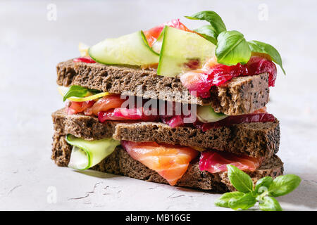 Sliced beetroot marinated salmon sandwiches with rye bread, cucumber, basil and lemon served in stack on wooden cutting board over grey blue texture b - Stock Photo