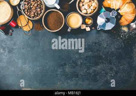 Coffee composition on dark background. Coffee espresso in dark cups, coffee beant, ground coffee, brown sugar, milk, croissants, capsules. Food frame  - Stock Photo