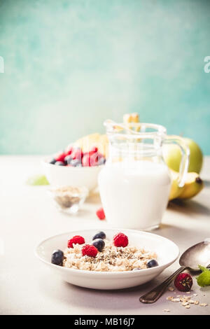 Oatmeal porridge with fresh berries, fruits and almond milk. Healthy breakfast, healthy eating, vegan food concept. - Stock Photo
