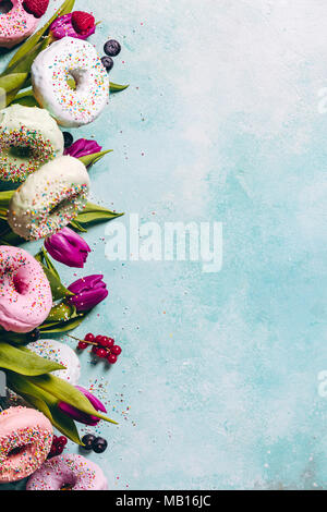 Sweet and colourful doughnuts with sprinkles, purple tulips and berries falling or flying in motion against blue pastel background. Border with space  - Stock Photo