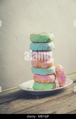A stack of donuts on wooden table against the wall - Stock Photo