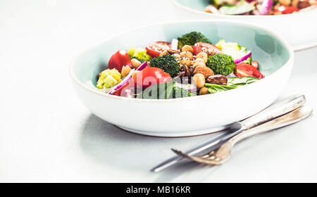 Healthy vegan energy boosting salad with chickpeas, broccoli, tomatoes, red onion, spinach and nuts in blue plate on concrete background, selective fo - Stock Photo