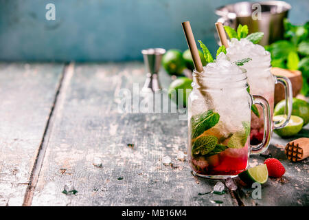 Mojito cocktail with lime, raspberry and mint in glass jars on the table. Copy space - Stock Photo