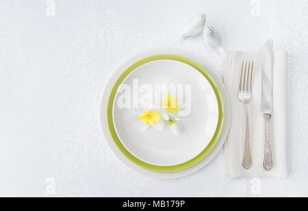 Classic serving for a gala dinner with luxurious porcelain, silverware and spring flowers on a white tablecloth, with copy-space - Stock Photo