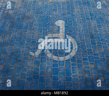 Top view on parking sign for disable people. Disabled parking space and wheelchair symbols on pavement - Stock Photo