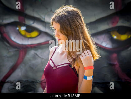 Pretty teen girl portrait, looks down, long hair, colorful grunge background wall. Half body portrait of beautiful Caucasian teenage girl in red top. - Stock Photo