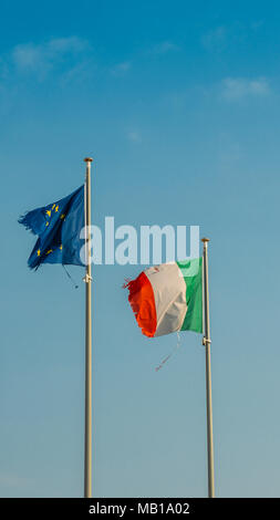 Italy flag and Europe flag waving together on a mast in isolated the blue sky background. Concept for financial treated, unique currency and financial bond despite the torn sides. - Stock Photo