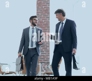 Confident business partners walking down in office building - Stock Photo