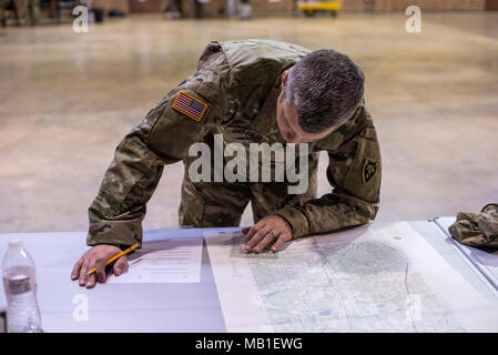 Army Staff Sgt. Jacob Bender, assigned to the 430th Explosive Ordinance Disposal unit, conducted a map reading test during the 60th Troop Command's (60th TC) Best Warrior Competition at the Claude T. Bowers Military Center in Raleigh, North Carolina, Feb. 10, 2018. The two-day competition tested the mental and physical strength of seven Soldiers, with one enlisted and one noncommissioned officer being selected to represent 60th TC during the state-level completion in March. - Stock Photo