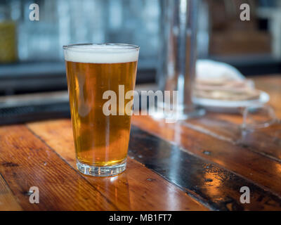 Full pint glass of beer sitting on bar counter ready to be drinked - Stock Photo