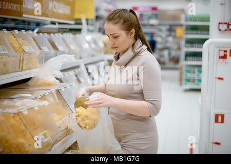 young beautiful woman buys chips on weight in grocery supermarket - Stock Photo