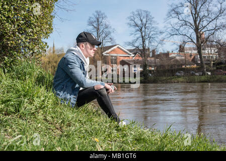 Young male youth sitting next to the river in the beautiful spring sunshine wearing denim jacket and black baseball hat - Stock Photo