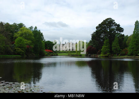 Sheffield Park House beside a lake with Rhododendrons - Stock Photo