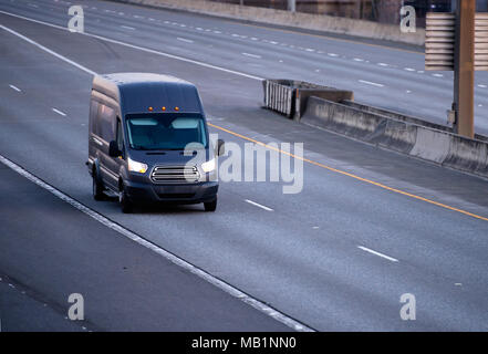 Black compact commercial useful small business cargo mini van running on the multiline road with turn on headlights to point of destination - Stock Photo
