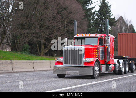 bright red power classic american big rig semi truck with tall chrome exhaust pipes transporting container