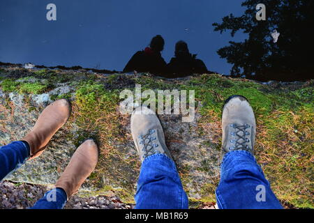 Two pairs of feet at edge of Crathes Mill Pond with reflection in water - Stock Photo