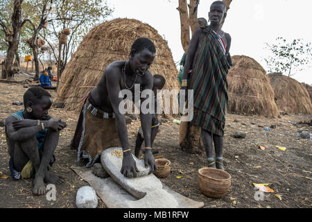 Omorate, Ethiopia - January 24, 2018: Women from Mursi tribe are grinding cereals with a stone to prepare flour in Ethiopia. - Stock Photo