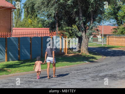 Johannesburg, South Africa - unidentified African mother and child in traditional dreadlocks hairstyles walk down a residential street in the city - Stock Photo