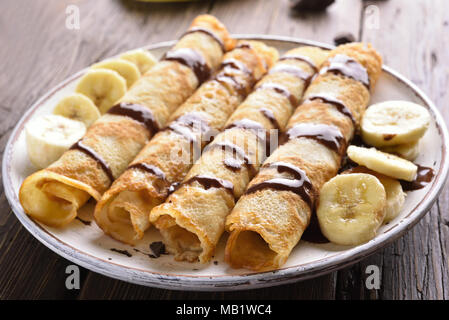 Crepes roll with banana slices on wooden table. Close up view - Stock Photo