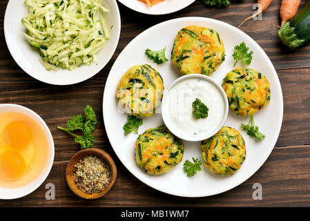 Tasty vegetable cutlet from carrot, zucchini, potato with sauce on wooden background. Top view, flat lay - Stock Photo