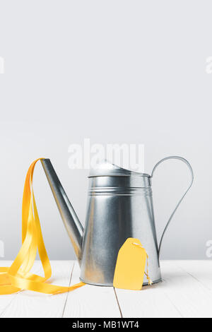 close-up view of shiny watering pot with yellow ribbon and blank tag on grey - Stock Photo