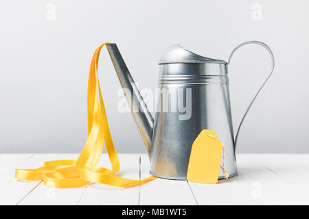 close-up view of shiny watering can with yellow ribbon and blank label on grey - Stock Photo