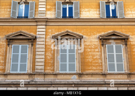 Blue shutters and weathered yellow painted walls on a building in the city of Rome, Italy. - Stock Photo