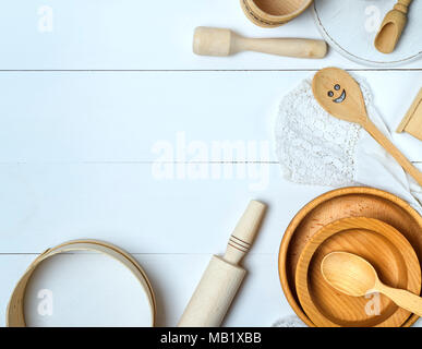 wooden  sieve and rolling pin, round cutting board and other kitchen items on a white table, top view, empty space - Stock Photo